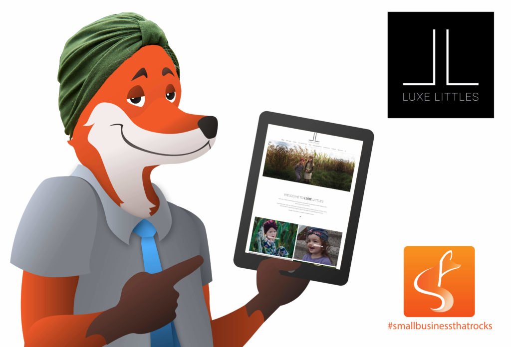 slyfox mascot holding tablet with luxe littles website
