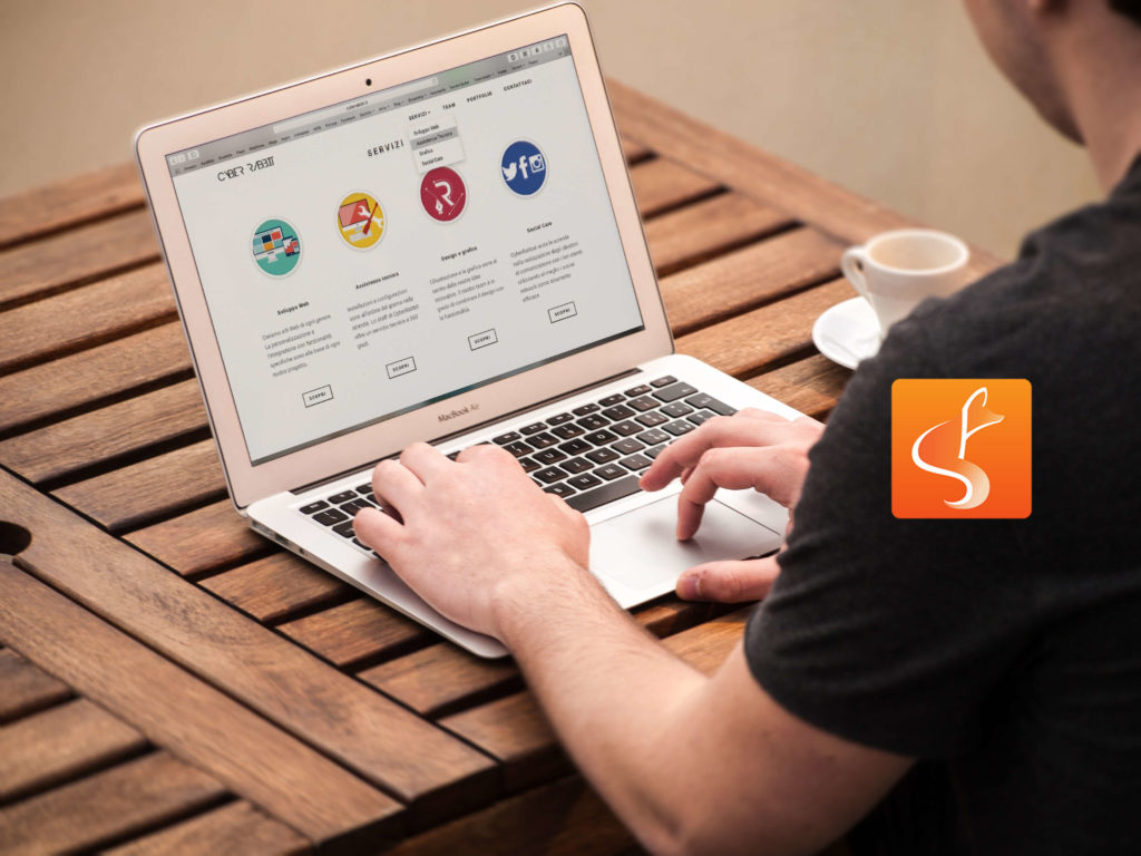 slyfox logo with man on laptop in background - SlyFox Web Design and Marketing